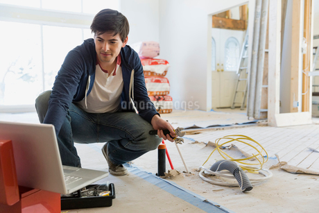 Young man consulting online advice for home renovationsの写真素材 [FYI02297608]
