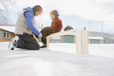 Father tying ice-skates for sonの写真素材 [FYI02297700]