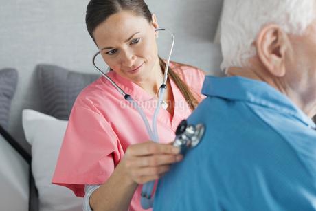 Home care nurse examining senior man with stethoscopeの写真素材 [FYI02297711]