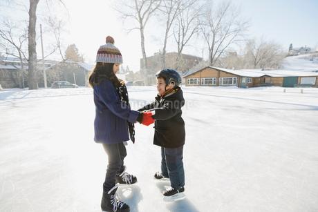 Siblings ice-skating on outdoor rinkの写真素材 [FYI02297825]
