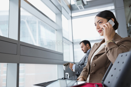 Businesswoman with mobile phone sitting in airportの写真素材 [FYI02297867]