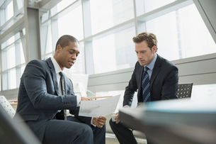 Businessmen discussing paperwork in officeの写真素材 [FYI02298039]