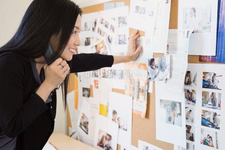 Businesswoman looking at bulletin board in officeの写真素材 [FYI02298090]