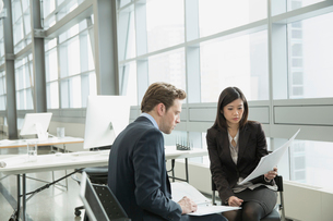 Business people reviewing paperwork in officeの写真素材 [FYI02298152]