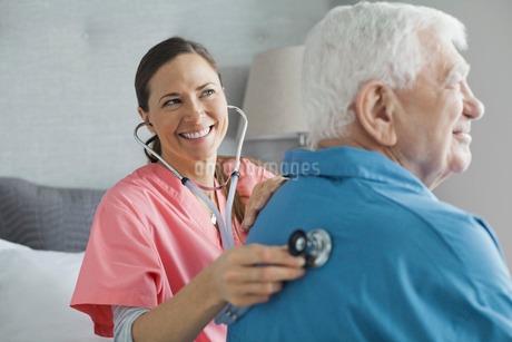 Home care nurse examining senior man with stethoscopeの写真素材 [FYI02298179]