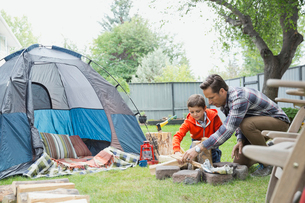 Father and son setting up backyard campfireの写真素材 [FYI02298316]