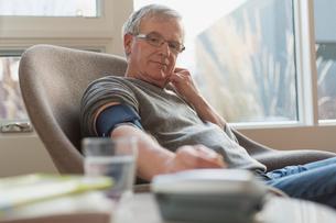 Senior man taking blood pressure at home.の写真素材 [FYI02298351]