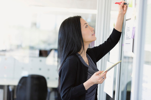 Businesswoman writing notes on project visuals in officeの写真素材 [FYI02298393]