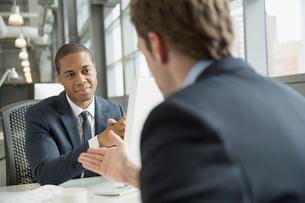 Businessmen talking at desk in officeの写真素材 [FYI02298470]