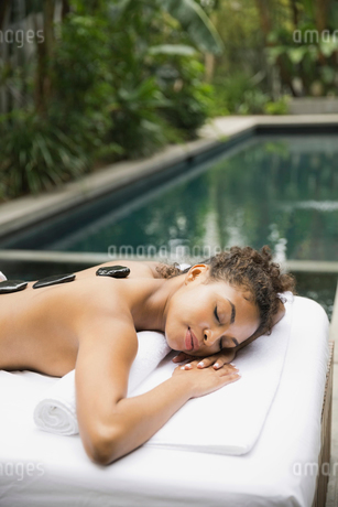 Relaxed woman receiving stone therapy at day spaの写真素材 [FYI02298501]