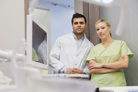 Portrait of confident dentist and assistant in officeの写真素材 [FYI02298506]