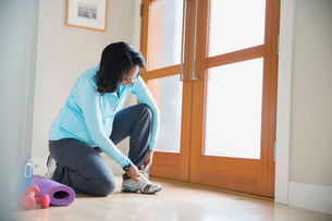 Pregnant woman with yoga mat tying shoeの写真素材 [FYI02298695]