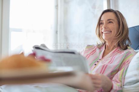 Senior woman reading newspaper in bedの写真素材 [FYI02298719]