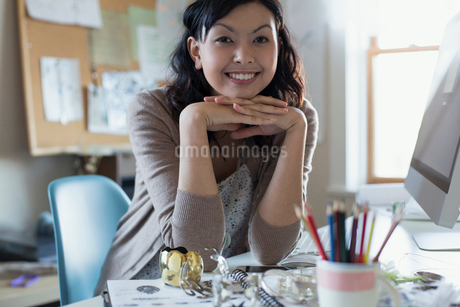 Portrait of beautiful female artist with chin on hands at deskの写真素材 [FYI02298757]