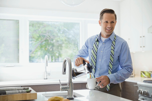 Smiling businessman pouring cup of coffeeの写真素材 [FYI02298816]