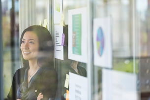 Smiling businesswoman leaning on glass wall in officeの写真素材 [FYI02298851]
