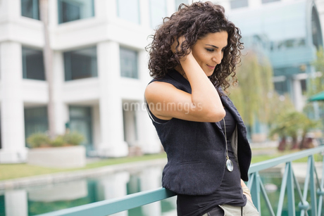 Thoughtful woman standing against railing outdoorsの写真素材 [FYI02298902]