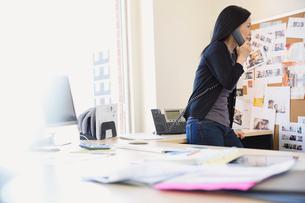 Businesswoman talking on telephone in officeの写真素材 [FYI02299032]