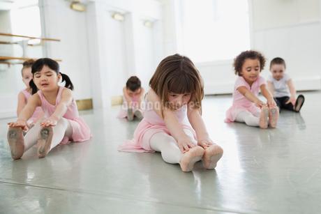 Children doing stretching exercises in ballet studioの写真素材 [FYI02299047]