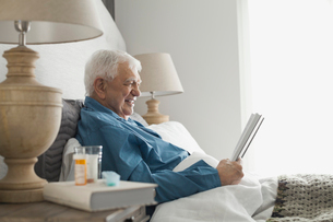 Senior home care patient sitting in bed readingの写真素材 [FYI02299126]