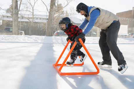 Son using assistant rack on ice hockey rinkの写真素材 [FYI02299271]