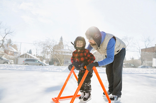 Son using assistant rack on ice hockey rinkの写真素材 [FYI02299300]