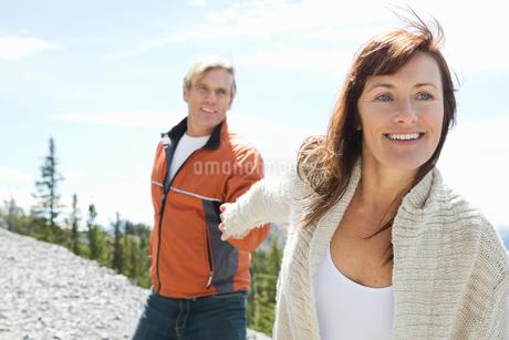 Happy mature couple holding hands on mountain peakの写真素材 [FYI02299305]