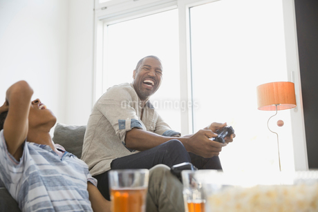 Father and son playing video games at homeの写真素材 [FYI02299318]