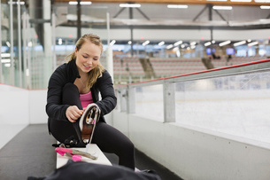 Female figure skater tying up skates in skating rinkの写真素材 [FYI02299344]