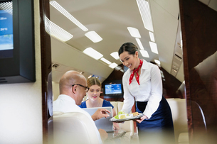 Flight attendant serving food to business colleagues in airplaneの写真素材 [FYI02299359]