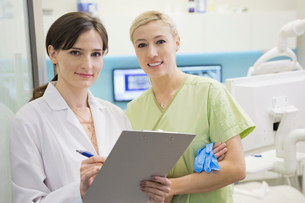 Portrait of confident dentist and assistant with clipboardの写真素材 [FYI02299426]