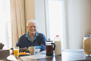 Portrait of happy senior man sitting at breakfast tableの写真素材 [FYI02299471]