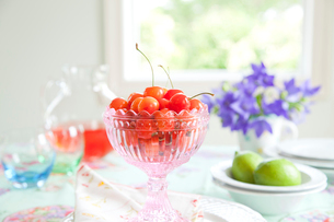 食卓のピンクのカットグラスのサクランボとキキョウの花の写真素材 [FYI02299484]