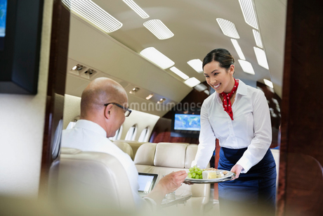 Flight attendant serving food to male passenger in airplaneの写真素材 [FYI02299489]