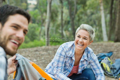 Couple smiling as they set up campの写真素材 [FYI02299553]