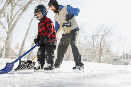 Father and son clearing snow from skating rink with shovelsの写真素材 [FYI02299679]