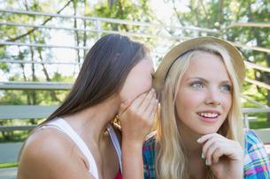 Teenage girl whispering to girl friendの写真素材 [FYI02299809]
