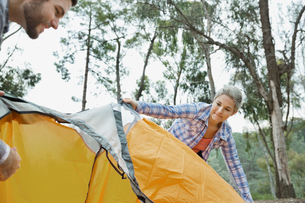Male and female campers setting up tent in forestの写真素材 [FYI02299990]