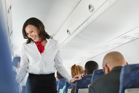 Flight attendant talking to passengers in airplaneの写真素材 [FYI02300103]