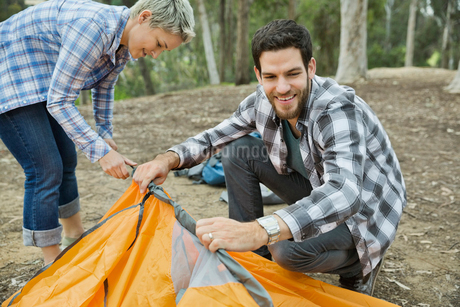 Couple setting up tent in forestの写真素材 [FYI02300106]