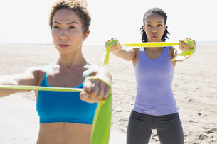Women exercising with resistance band on beachの写真素材 [FYI02300248]