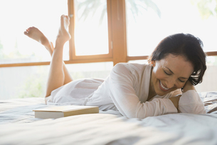 Portrait of smiling woman lying on bedの写真素材 [FYI02300260]