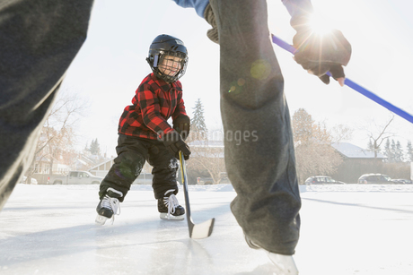 Father and son playing ice hockey on rinkの写真素材 [FYI02300300]