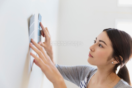 Young woman choosing paint colors at homeの写真素材 [FYI02300309]