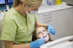 Dental assistant flossing girls teethの写真素材 [FYI02300382]