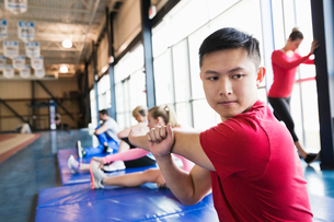 Man stretching on mat in fitness centerの写真素材 [FYI02300414]