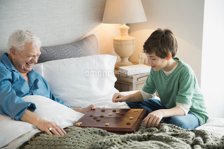 Grandfather and grandson playing checkers in bedroomの写真素材 [FYI02300436]
