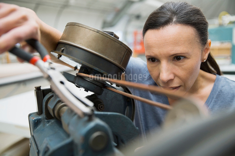 Worker using machinery in textile manufacturing plantの写真素材 [FYI02300499]