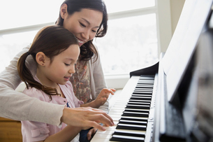 Mother teaching daughter to play pianoの写真素材 [FYI02300575]