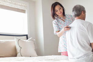 Female nurse examining senior man with stethoscope at homeの写真素材 [FYI02300583]